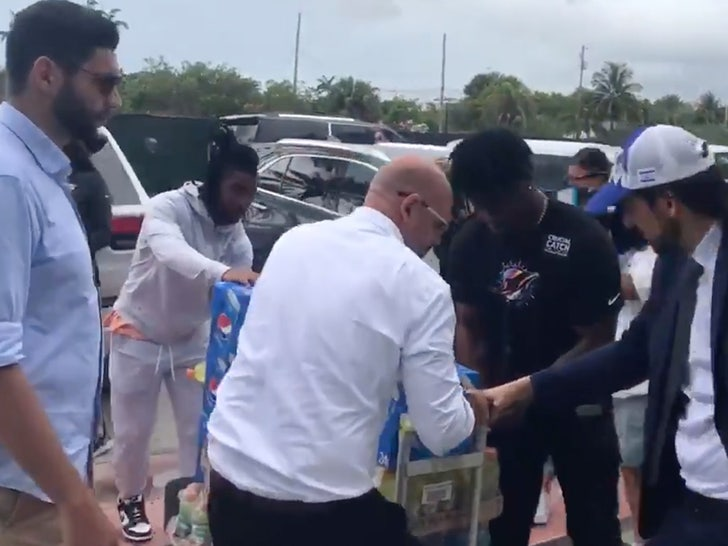 dolphins players helping unload