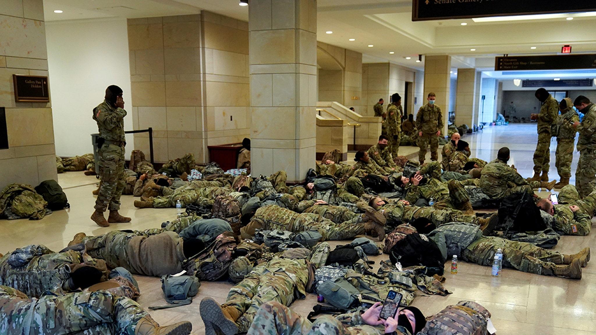 Измученные вооруженные члены Национальной гвардии спят на этаже Капитолия