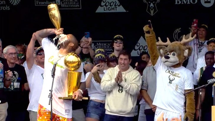 P.J. Tucker Chugs From Huge Champagne Bottle At Bucks' Championship Parade.jpg